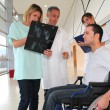 Medical team with handicapped person looking at X-ray — Stock Photo #18225953