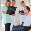 Medical team with handicapped person looking at X-ray — Stock Photo