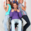 Young man in wheelchair with group of girl friends - Stockfoto