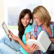 Girlfriends reading book on electronic pad - Stock fotografie