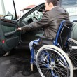 Stock Photo: Young man in wheelchair getting in his car
