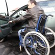 Young man in wheelchair getting in his car — Stock Photo #18226635