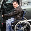 Young man in wheelchair getting in his car - Stok fotoğraf