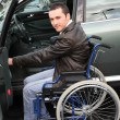 Young man in wheelchair getting in his car - Стоковая фотография