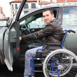 Stock Photo: Young min wheelchair getting in his car