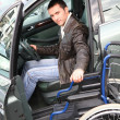 Young man in wheelchair getting in his car — Stockfoto