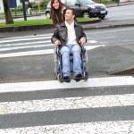 kvinna hjälpande vän i rullstol över gatan — Stockfoto