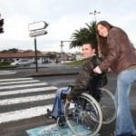 Woman helping friend in wheelchair cross the street — Stock Photo #18226717