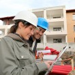 Stock Photo: Architect and engineer looking at plan on construction site