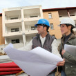 Architect and engineer looking at plan on construction site — Stock Photo #18226743