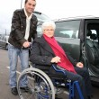 Young man assisting senior woman in wheelchair — Stock Photo