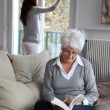 Elderly woman reading book while housekeeper cleans windows — Stock Photo