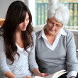 Young woman reading book to elderly woman — Stock Photo