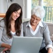 Young woman and elderly woman with laptop computer — Foto de Stock