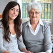 Stock Photo: Young woman reading book to elderly woman