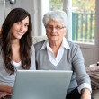 Young woman and elderly woman with laptop computer — Stock Photo #18226875