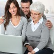 Elderly woman with grandchildren looking at laptop computer — Stock Photo
