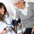 Closeup of nurse checking senior woman blood pressure — Stock Photo #18226997