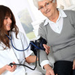 Stock Photo: Closeup of nurse checking senior woman blood pressure