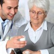 Stock Photo: Doctor explaining drugs prescription to elderly woman