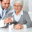 Doctor explaining drugs prescription to elderly woman - Stock Photo