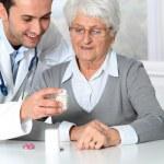Doctor explaining drugs prescription to elderly woman — Stock Photo