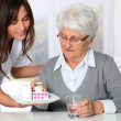 Nurse bringing medicine to elderly woman - Stock Photo