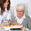 Stock Photo: Beautiful nurse bringing meal tray to old womat nursing home