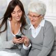 Young woman showing how to use mobile phone to grandmother — Stock Photo #18227111