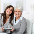 Young woman playing video game with grandmother — Stock Photo #18227153