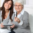 Young woman playing video game with grandmother - Stock Photo