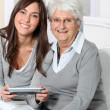 Young woman playing video game with grandmother — Stock Photo