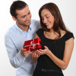 Man offering present to girlfriend — Stock Photo #18227455