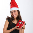 Woman with Santa hat holding Christmas present — Stock Photo