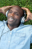 Man laying down in garden with headphones on — Stock Photo