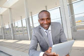 Salesman on business travel using electronic tablet — Stock Photo