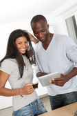 Young couple using electronic pad in kitchen — Stock Photo