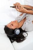 Schöne lateinische mädchen hören von musik mit kopfhörer — Stockfoto