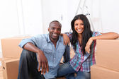 Cheerful couple sitting in empty new house — Stock Photo