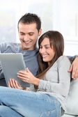 Couple sitting on sofa with electronic pad — Stock Photo