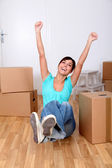 Beautiful young woman sitting next to boxes in new house — Stock Photo