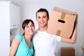 Young couple carrying boxes into new house — 图库照片