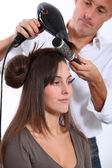 Hairdresser drying woman's hair — Stock Photo