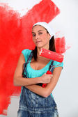 Young woman painting house wall in red — Stock Photo