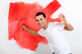 Young man painting house wall in red — Stock Photo