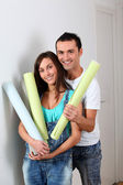 Closeup of young couple holding wallpaper rolls — Stock Photo