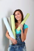 Beautiful young woman holding wallpaper rolls — Stock Photo