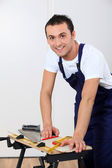 Young man working wood on workbench — Stock Photo