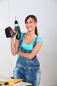Young woman holding electric drill — Stock Photo