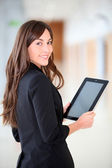 Businesswoman standing in hall with electronic pad — Stock Photo